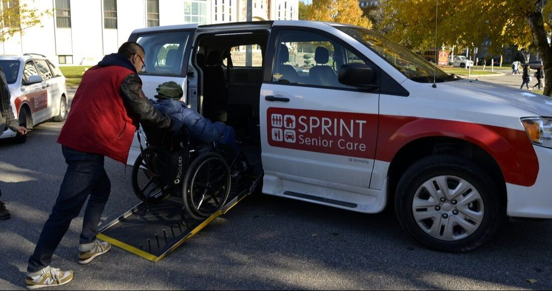wheelchair client being pushed up ramp into van